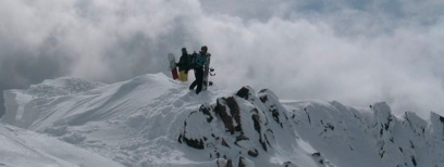 Snowboarders hiking on snowy ridge